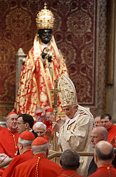 ST. PETER'S BASILICA--Pope Benedict XVI waved as he arrived to concelebrate Mass with 22 new cardinals in St. Peter's Basilica at the Vatican Feb. 19. The statue of St. Peter in the background is decorated for the celebration of the feast of the Chair of St. Peter. (CNS photo /Paul Haring)