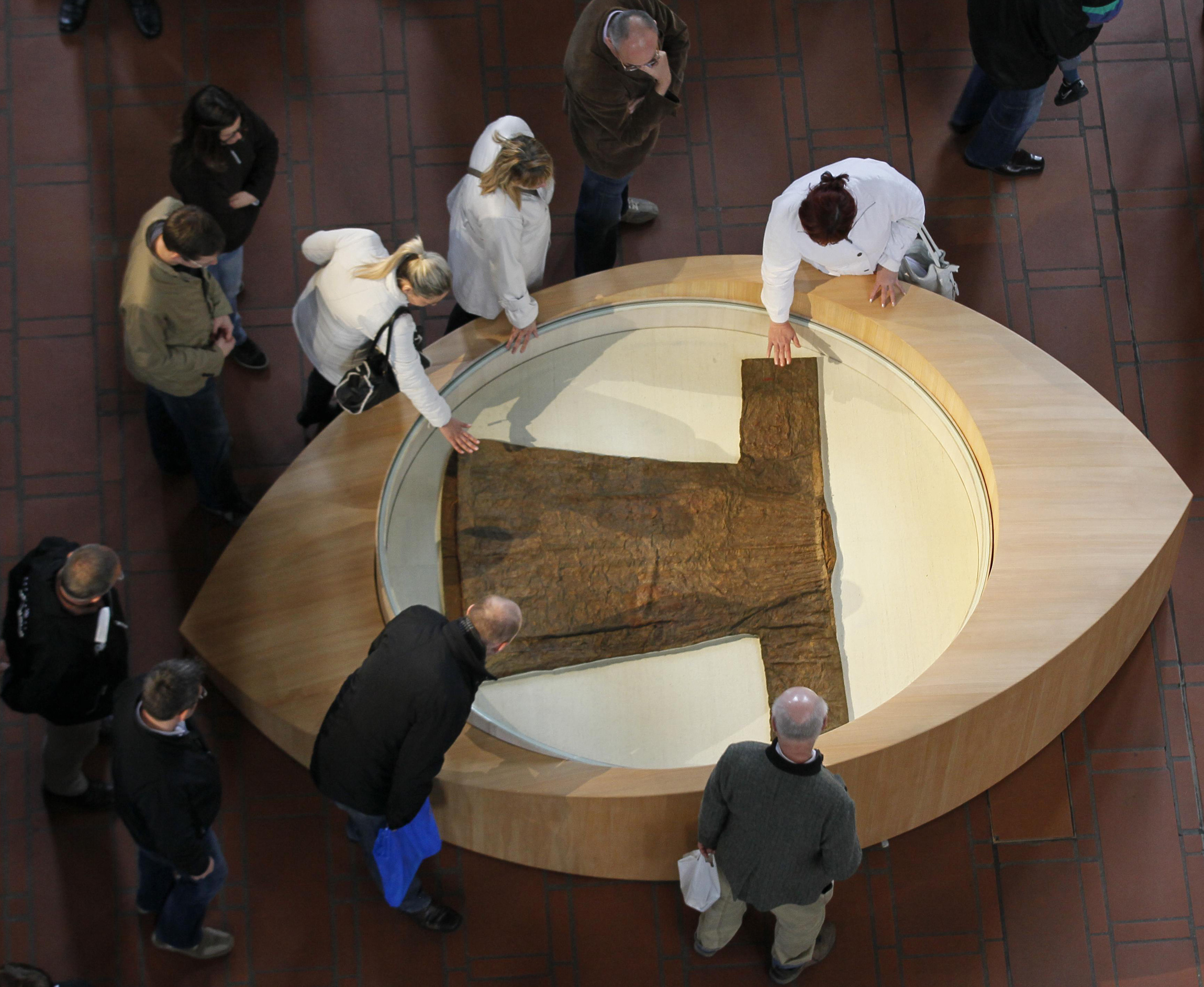 "PILGRIMS TOUCH CASING CONTAINING ROBE REPORTEDLY WORN BY CHRIST ON DISPLAY AT CATHEDRAL IN GERMANY--Pilgrims touched a casing containing the ""'Holy Robe"" in the cathedral in Trier, Germany, April 15. The ancient town of Trier marks the 500th anniversary of the first public appearance of the Seamless Robe of Jesus, reportedly worn during, or shortly before his crucifixion. Some 500,000 pilgrims are expected to visit the relic through May 13. (CNS photo/Wolfgang Rattay, Reuters)"