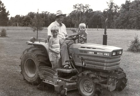 ONCE A FARMER--Fr. Syl Bauer is pictured in this 1989 file photo on a tractor with two children. Fr. Bauer grew up on a farm in Freeburg, MO. (The Mirror)