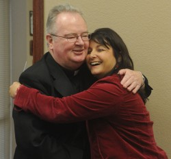 ST. MARY PARISH AWARDED GRANT—Fr. Justin Monaghan, pastor, hugged Stephanie Howard, chairman of the board for the Community Foundation of the Ozarks, on Nov. 27, 2013, after she announced a grant of $300,000 for the rebuilding of the St. Mary Catholic Church and School. (Photo by Roger Nomer)