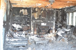 LIVING ROOM OF ST. MARY RECTORY—A photo captured what remains of St. Mary Parish rectory after a fire and burglary at the West Plains parish Saturday night, June 21, 2014. The one occupant of the dwelling at the time of the blaze, associate pastor Fr. Augustine Lourduswami, managed to escape with minor injuries after knocking out a bedroom window. (Photo by Fr. Joseph Weidenbenner)