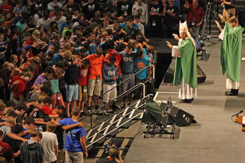 VOCATION DISCERNMENT—Aux. Bp. Edward Rice of the Archdiocese of St. Louis prayed over a group of young men who stepped forward toward the end of the closing liturgy of the Steubenville Youth Conference held Sun., July 20, to express their openness to a calling to the ordained priesthood. (Photo by J.B. Kelly)