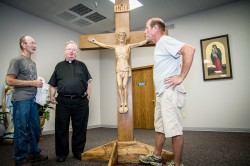 CRUCIFIX REPAIRED AND BACK TO PARISH—Louis Ochsenbein, Fr. Justin Monaghan, pastor, and Ivan Eck paused after getting the newly-repaired crucifix into its new stand at the temporary location of St. Mary Catholic Church, Joplin. The crucifix, the original that had hung in St. Mary's sanctuary since 1968, was unearthed in the 2011 tornado debris, astonishingly only mildly damaged.(Photo by Anne Brown, Joplin Globe)