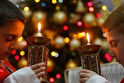 Human and divine—Two Iraqi boys hold candles as they pray for peace in Iraq and Syria during Mass in a Chaldean Catholic church in Amman, Jordan. The Christmas season is a liturgical season that begins on Christmas and ends with the feast Baptism of the Lord, Jan. 11, 2015. (CNS photo/Ali Jarekji, Reuters)