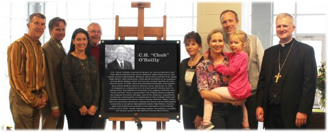 """THE O'REILLY FAMILY—David O'Reilly, Tim O'Reilly, Brooke O'Reilly, Charlie O'Reilly, Mary Beth O'Reilly, Lindsay O'Reilly - French, Landree French (held), Justin French, and Bp. James V. Johnston were photographed surrounding a plaque that will remain in Springfield Catholic High School in memory of C.H. """"Chub"""" O'Reilly, Sr., and his long-standing commitment to Springfield Catholic Schools. The late benefactor's trust recently distributed a generous gift to Springfield Catholic Schools for the purpose of satisfying the remaining balance of the Springfield Catholic High School Capital Campaign.(Submitted photo)"""