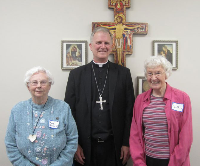 JUBILARIANS—During the annual Gathering with Religious of the Diocese, Bp. James V. Johnston posed for a photo with consecrated women religious celebrating significant milestones in ministry: Sr. Mary Elizabeth Runde, SSND, 60 years, St. Cecilia Parish, Kennett, MO; Bishop Johnston; Sr. Cynthia Brinkman, SSND, 60 years, Casa Guadalupe Family Growth Center, Ellington, MO. (Photo by Sr. Jeanne Goessling)