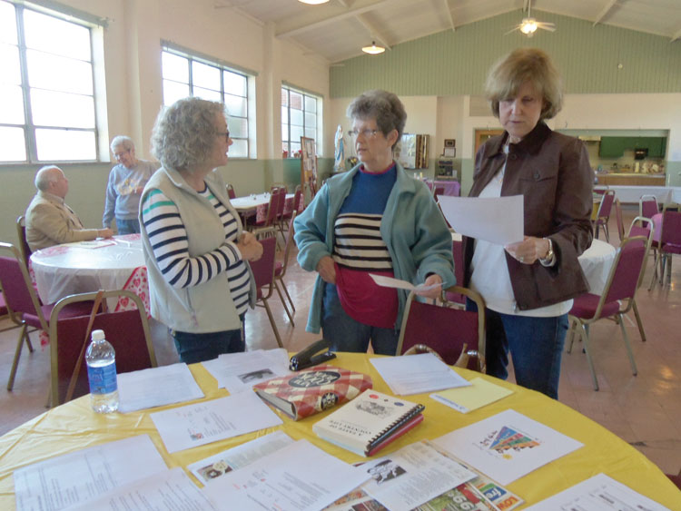 RESOURCES—Beverly Tipton, Jane Medlin, and Nancy Luber reviewed table materials for the April 2 community day held at Sacred Heart Parish, Caruthersville. Parishioners are performing intentional acts of mercy during this Jubilee Year of Mercy, assisting many in the community. (The Mirror)