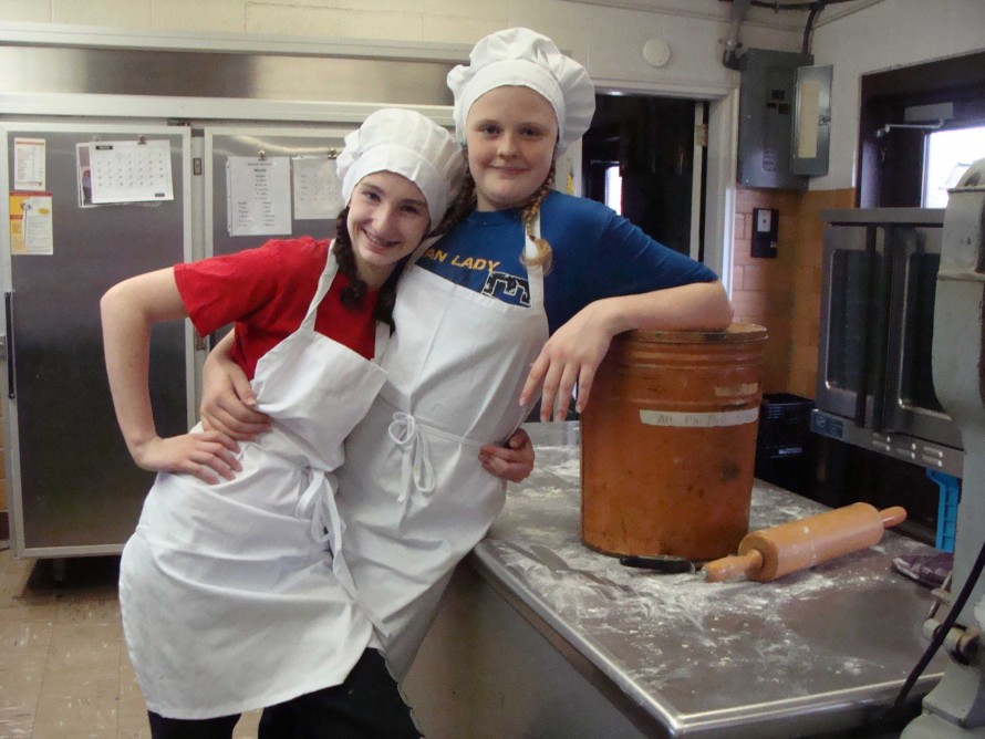 COOKS FOR THE DAY—Kennedi McVay and Katie Webb looked professional in their chef hats and aprons on March 29 when they cooked dumplings for the entire student body. (Submitted photo)