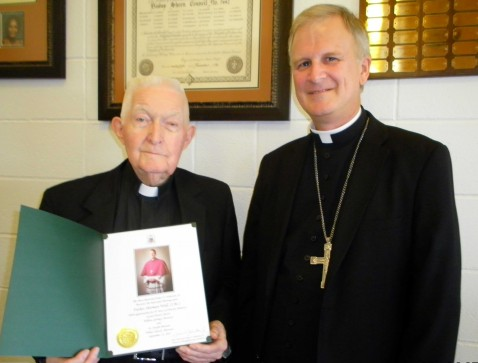 FR. WALL HONORED—The Most Reverend James V. Johnston recently commended Fr. Sherman Wall, OMI, for his 30 years of service in Sacred Heart Parish, Willow Springs, and St. Joseph Mission Church, in White Church. A priest of the Oblates of Mary Immaculate, Fr. Wall was pictured holding his episcopal blessing from Bp.-designate Johnston. In addition to serving as pastor of both faith communities, Fr. Wall continues to be active with the area Ministerial Alliance and Missourians United to Combat Hunger (MUNCH).(Submitted photo)