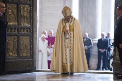 HOLY YEAR OF MERCY—Pope Francis prayed after opening the Holy Door in St. Peter's Basilica Dec. 8, 2015, launching the extraordinary jubilee of mercy. Photo credit: LOsservatore Romano)