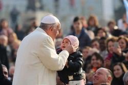 AUDIENCE—Pope Francis kissed a child in St. Peter's Square for the general audience, Dec. 9, 2015. (Photo by Daniel Ibanez/CNA)