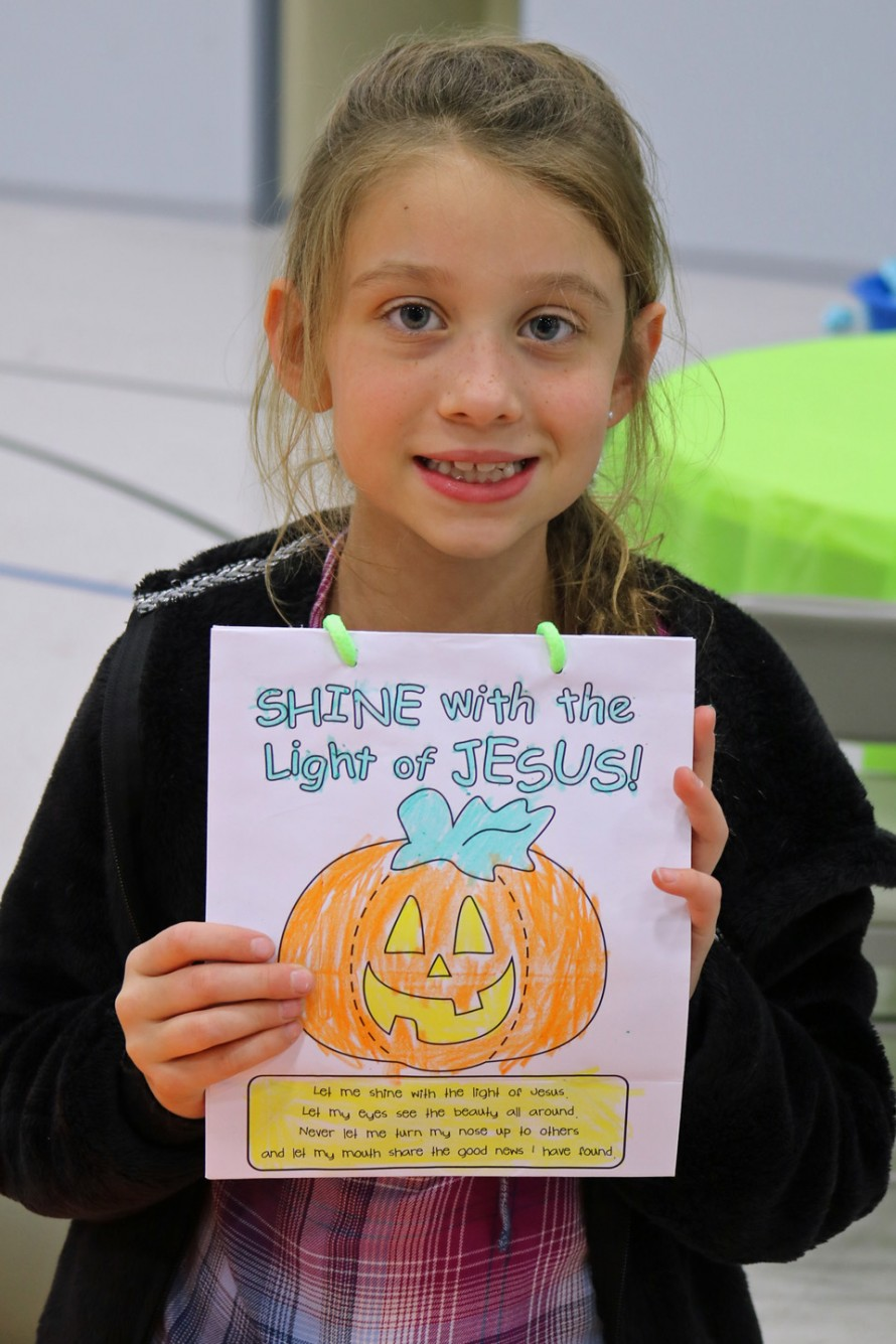 """CRAFTS & GAMES—Saint Joseph the Worker parishioner Summer Lawrence, third grade, displayed a Shine with the Light of Jesus candy and prize bag she decorated for the """"March of the Saints"""" party on Nov. 1. (Photo by J.B. Kelly/The Mirror)"""