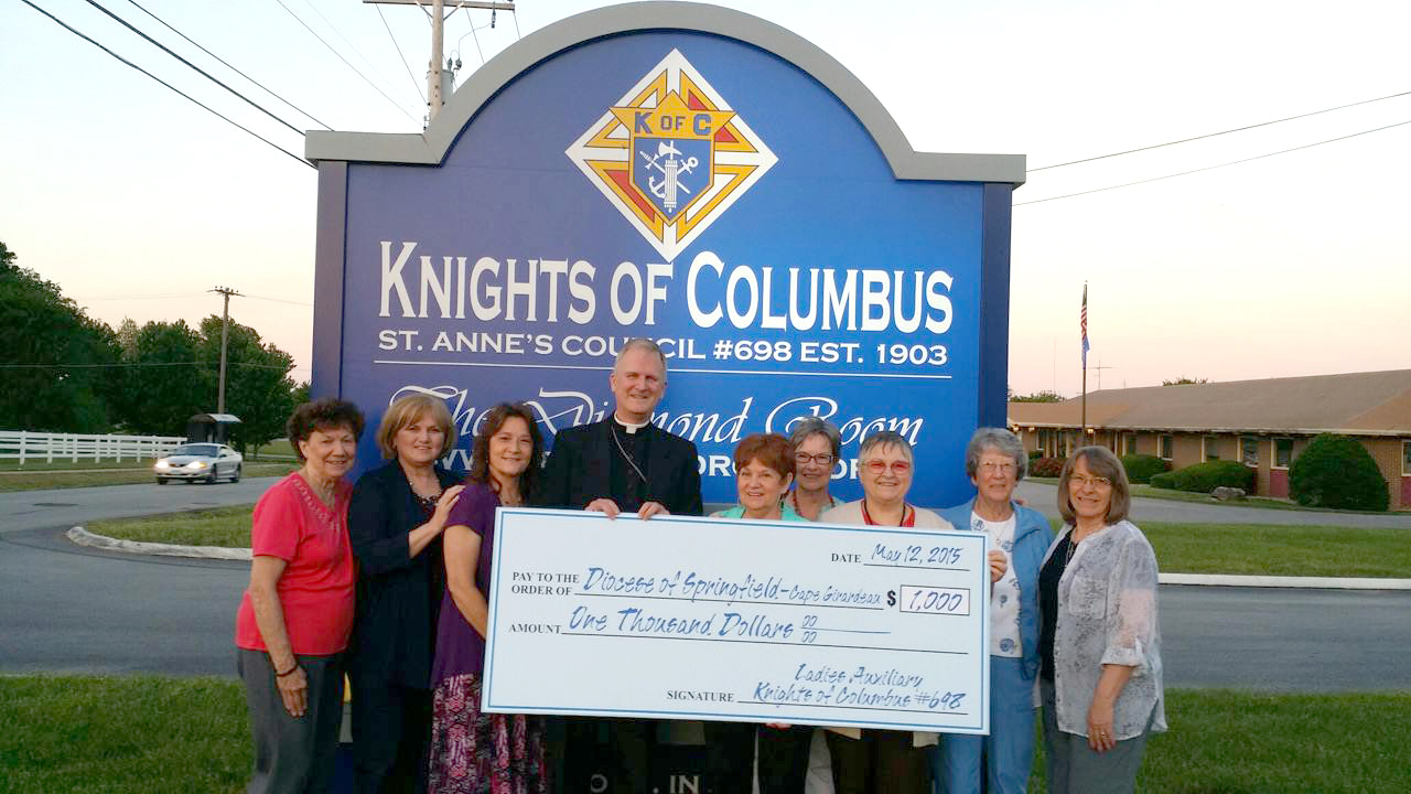 LADIES AUXILIARY—Knights of Columbus Council #698 Ladies Auxiliary members presented Bishop James V. Johnston with a check on May 12. Pictured were: Carol Haselhorst, Sarah Pittman, Shelly Ferry, Bishop Johnston, Shirley Hart, Karen Carrol, Judy Rippee, Edie Enos and Marcella Fletcher. (Submitted photo)
