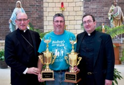 TRAVELING TROPHIES—Bishop Edward Rice presented the 2016 Bishop's Walk traveling trophies to Tim Pashia, St. Mary Church, Lamar, and to pastor Fr. Patrick Teter. Held annually, the 2017 Bishop's Walk is being held diocesan-wide April 1 & 2. (The Mirror)