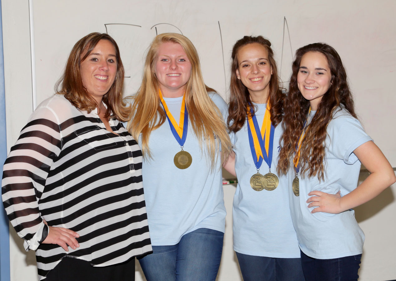 BUSY WITH BUSINESS—Mrs. Amanda Walker, Head of the McAuley Catholic High School Business Department, congratulate Miranda Green, Bailey Welch, and Kristin Metts for their outstanding work in the annual F.B.L.A. competition in Joplin. Miranda Green and Bailey Welch placed Third in the Sports Management Marketing category and Bailey Welch and Kristin Metts placed Third in the Hospitality Management category. (The Mirror)
