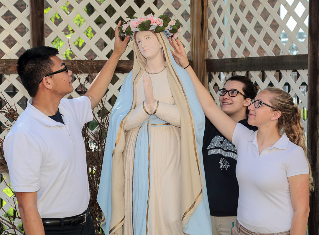 FOR LOVE OF MARY—McAuley Catholic High School students James Nguyen, Olivia Powell, and Chloe Kenkel, crown the Blessed Virgin Mary during the school's annual May Crowning. Students were involved in prayer and song during the presentation of the Crown of Flowers. (The Mirror)