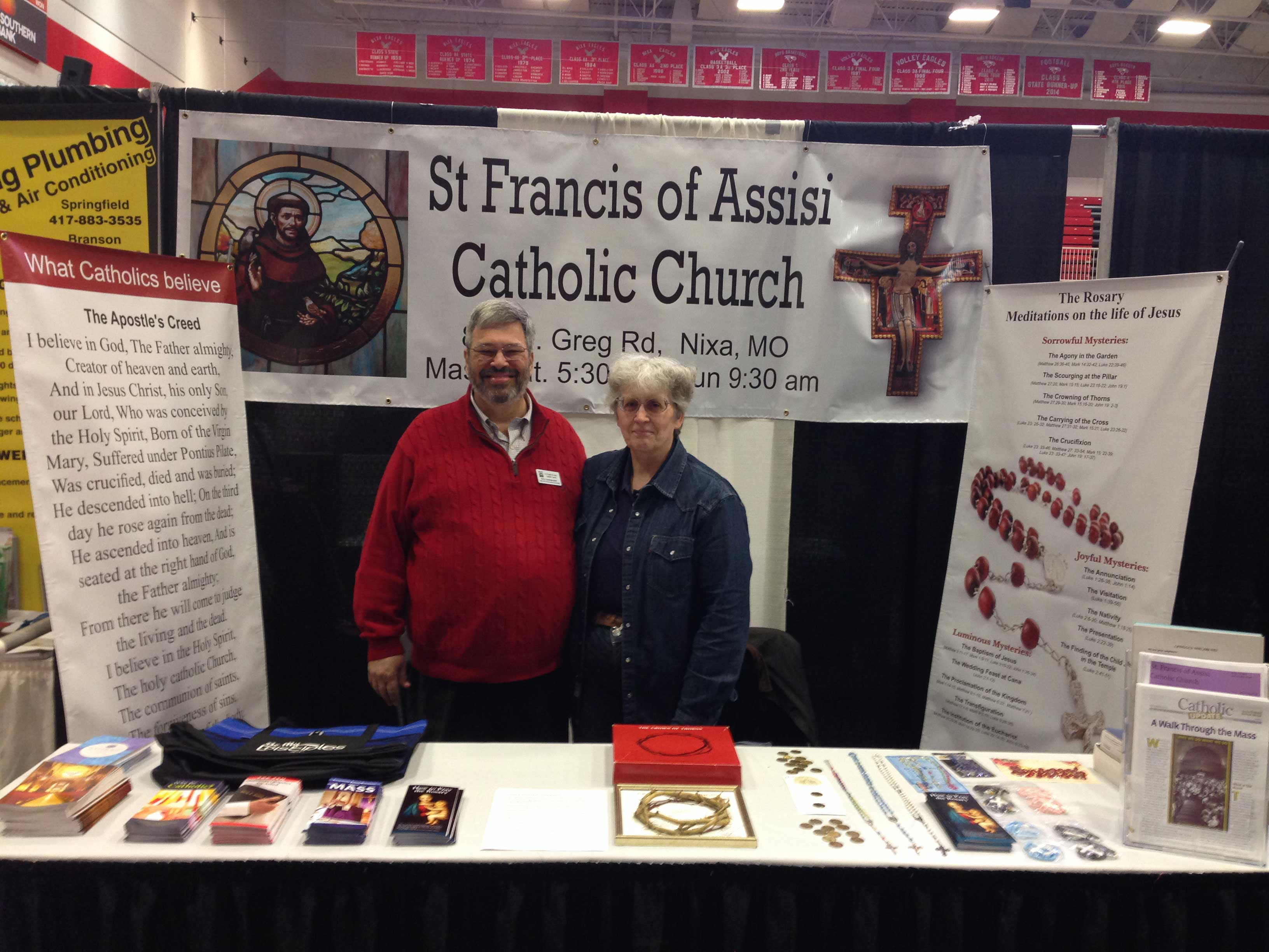 "ST. FRANCIS OF ASSISI PARISH—Rick and Diane Barnhart staffed the St. Francis of Assisi Parish booth at the Nixa Chamber of Commerce ""NIXPO"" event on Sat., March 18. They had materials available, answered questions about the faith, and invited those without a spiritual home to visit the parish for 9:30 a.m. Sunday Mass. Barnhart serves the parish as part-time Director of Religious Education. He also serves the diocese as part-time Associate Director of Religious Education and Catechesis. (Submitted photo)"