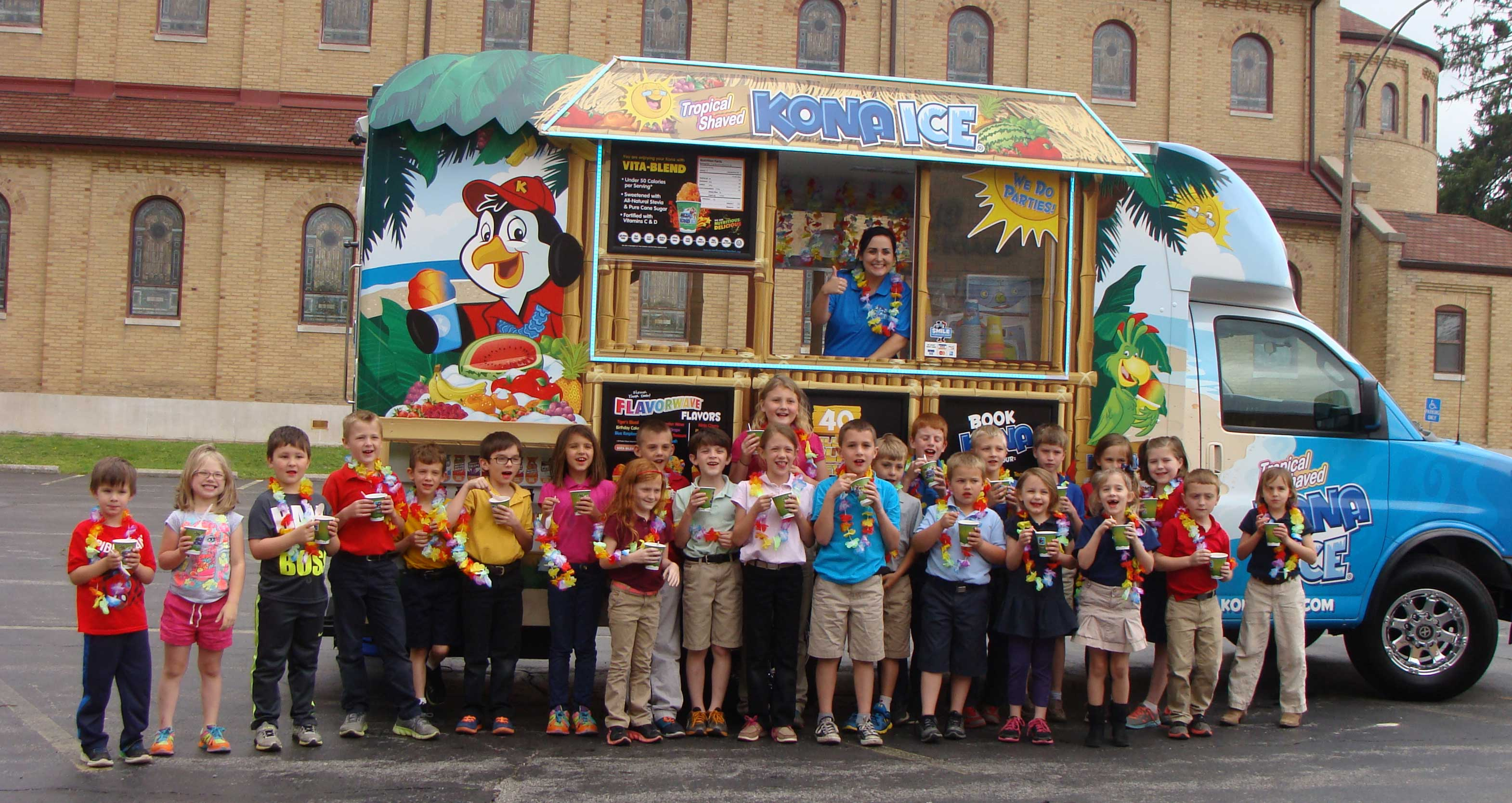 SHAVED ICE TREATS—Guardian Angel School students in preschool through third grade took a picture in front of the Kona Ice truck from Dexter, MO. The April 26 event was donated to and purchased at the school's annual dinner and auction in February. (Submitted photo)