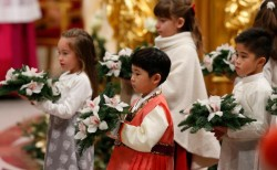 PAPAL SCHEDULE—Children carried flowers in procession as Pope Francis concluded the celebration of Christmas Eve Mass in St. Peter's Basilica Dec. 24, 2014. (CNS photo/Paul Haring)