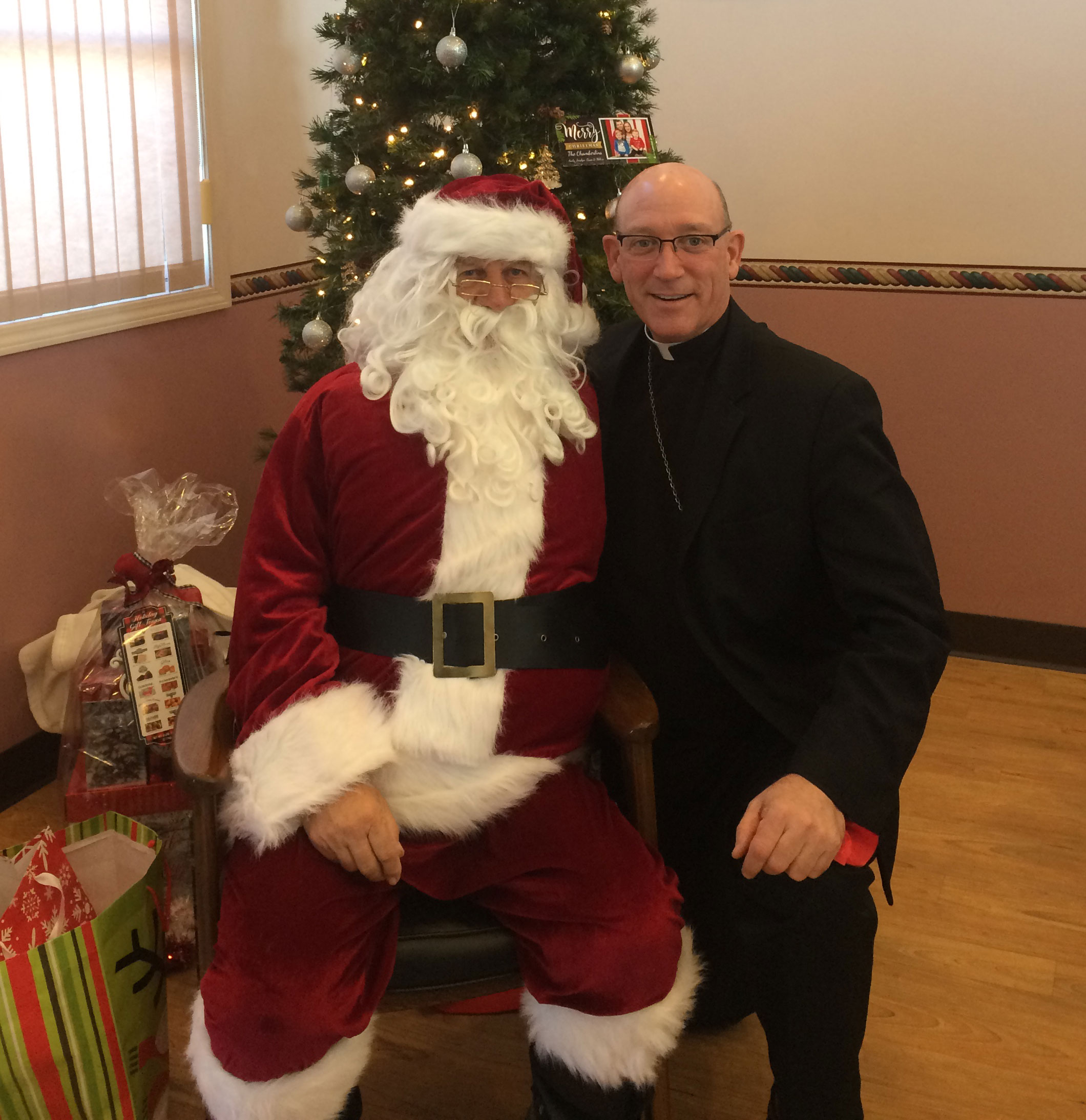 SANTA VISIT--Santa stopped in at Queen of Angels daycare to see the children. Bishop Rice helped pass out treats and gifts for the youth Dec. 20 before the Christmas Pageant under the direction of the Congregation of Mary, Queen. (The Mirror)