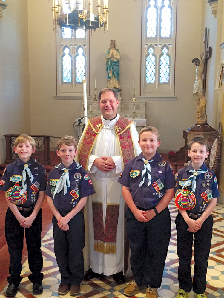 "PARVULI DEI—Those receiving the ""Parvuli Dei"" emblem from Fr. Allan Saunders were Kyle Boehme, Nicholas Gaeta, Jacob Mahnke, and Aidan Stiegemeyer. The Parvuli Dei (Children of God) is designed to help the Scout discover God in his daily life, to develop a good positive self-image, and to aid him in his awareness of the responsibilities that grow out of God's love for him. (Not pictured: Ethan Jackson). (Photo by Mary Ann Hennecke)"