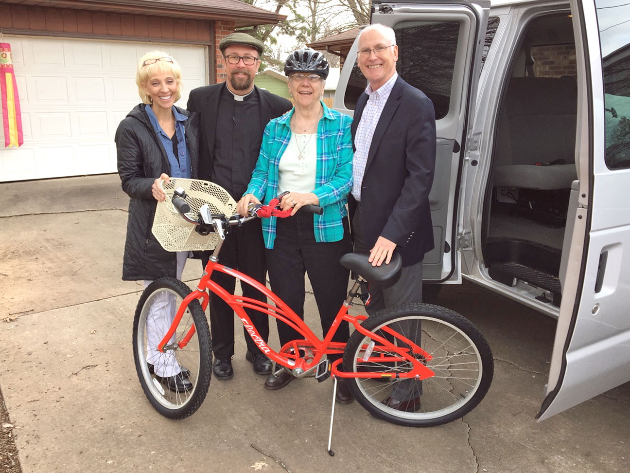 "NEW 'CRUISER' FOR SISTER—Sister Frances Wessel, SSND, recently had her bicycle stolen while she was on a ministry visit at Mercy Hospital in Springfield. Her 'parish family' of St. Joseph the Worker in Ozark held a 'fill-the-boot' fundraiser after Masses the weekend of Jan. 14-15 to assist Sr. Wessel with her lack of transportation. The parish raised enough money to buy her a brand-new, ""sacred-heart-red""colored 'cruiser,' complete with basket, bell, lights, helmet, and a bike-lock. The bicycle was delivered on Jan. 18 and blessed by Fr. Scott Sunnenberg, pastor. Pictured were Carol Craig, St. Joseph the Worker Parish secretary, Fr. Sunnenberg, Sr. Wessel, and Bill Hennessey, Parish Council Member and Vice President of Mission Services at Mercy Springfield. This is a perfect example of the 'love of one's neighbor' Msgr. Pope speaks about in this article. (Photo by J.B. Kelly/The Mirror)"