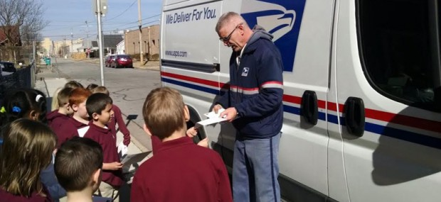 SEALED WITH A KISS—The USPS mail carrier helped kindergarten and first grade students in St. Joseph Catholic Academy, Springfield, place postage on the love letters they wrote to their parents for Valentine's Day during their Community Helpers unit. (The Mirror)