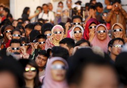 WOMEN LEADERS—Women watched a solar eclipse March 9 outside the planetarium in Jakarta, Indonesia. (CNS photo/Garry Lotulung, Reuters)