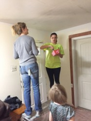 LOVE IN ACTION—Lori Powderly and Michelle Pappas mudded the ceiling in a flood-damaged home as the homeowner's daughter watched. The bible study group volunteers with Catholic Charities one Friday a month. (The Mirror)