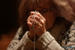 ADORATION—A woman prayed the rosary. There are different ways to spend time at Eucharistic Adoration. (The Mirror)